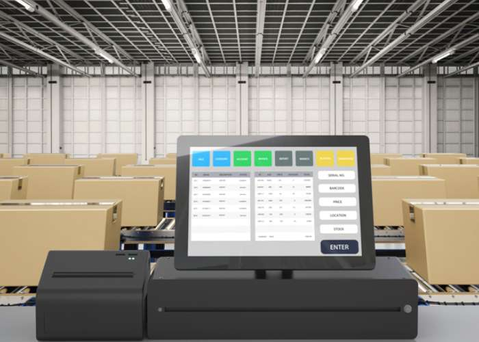 Image of a computer on a table overlooking boxes in a warehouse. Image used on Specialty Fulfillment's inventory management page.